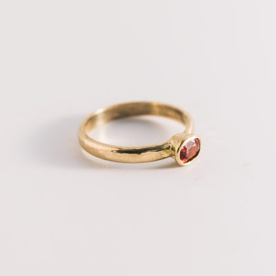 Orange sapphire set into a gold band